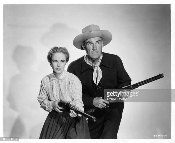 Jocelyn Brando and Randolph Scott hold guns in publicity portrait for the film 'Ten Wanted Men' 1955