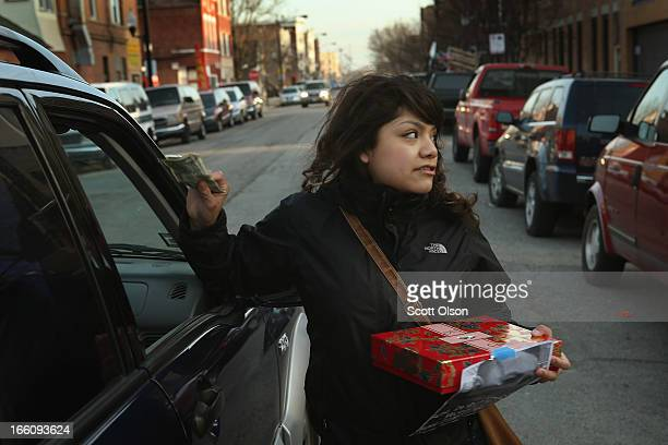 Jocelyn Ramos solicits donations from passersby to help pay for a funeral for her 14yearold friend Michael Orozco on April 8 2013 in Chicago Illinois...