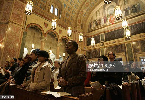 Jocelyne do Sacramento joins parishioners during the Holy Thursday service at the Cathedral of St. Matthew March 24, 2005 in Washington, DC. Cardinal...