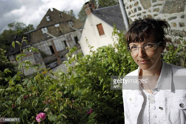 Jocelyne Guillemin president of the association 'Vivre sans amiante à Caligny' poses in her garden on June 21 2012 located next to the disused...