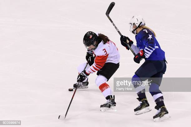 Jocelyne Larocque of Canada controls the puck against Monique LamoureuxMorando of the United States during the Women's Gold Medal Game on day...