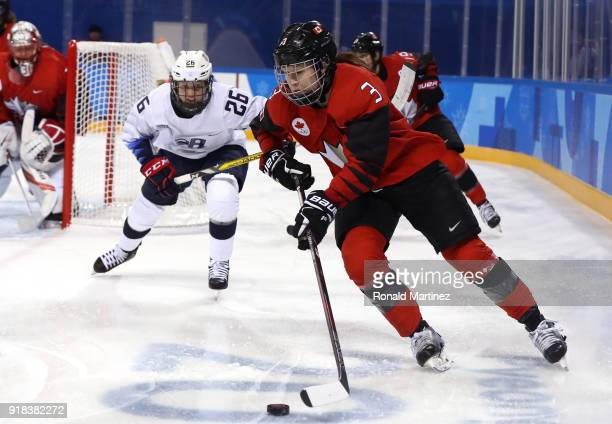 Jocelyne Larocque of Canada handles the puck against Kendall Coyne of the United States in the first period during the Women's Ice Hockey Preliminary...