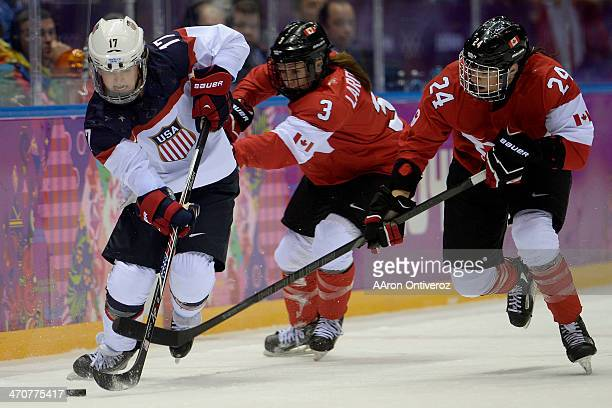 Jocelyne Larocque of the Canada and Natalie Spooner defend Jocelyne Lamoureaux of the USA during the third period of the women's gold medal ice...