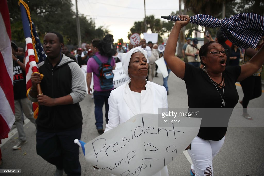Jocelyne Pierre and Yanick Gorneo (L-R) join with others to mark the 8th anniversary of the massive earthquake in Haiti and to condemn President Donald Trump's reported statement about immigrants from Haiti, Africa and El Salvador on January 12, 2018 in Miami, Florida. President Trump is reported to have called those places 'shithole countries' whose inhabitants are not desirable for U.S. immigration.