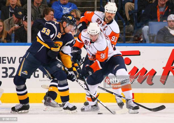 Jochen Hecht of the Buffalo Sabres battles for the puck with John Tavares and Doug Weight of the New York Islanders on October 16, 2009 at HSBC Arena...