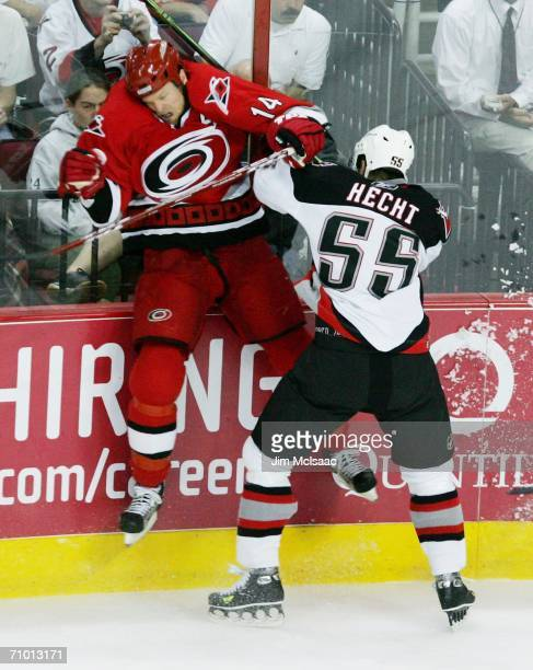 Jochen Hecht of the Buffalo Sabres hits Kevyn Adams of the Carolina Hurricanes in game two of the Eastern Conference Finals during the 2006 NHL...