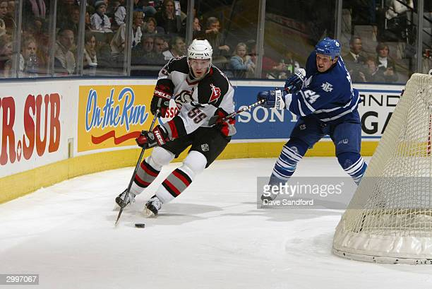Jochen Hecht of the Buffalo Sabres is pressured by defenseman Bryan McCabe of the Toronto Maple Leafs during the game at Air Canada Centre on...