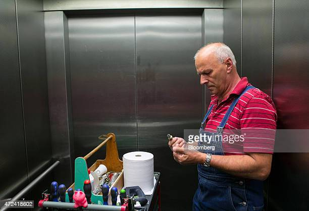 Jochen Heyn a 63yearold pensioner stands beside a tool cart as he travels in an elevator in an office building where he works 5 1/2 hours a week as a...