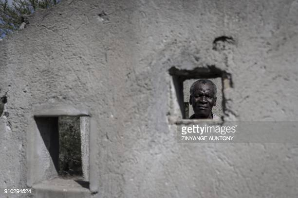 Jochonia Moyo a survivor of the 'Gukurahundi' killings pose for a photograph on December 20 2017 showing how people were packed into one holding cell...