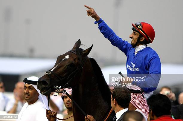 Jockey Ahmed Ajtebi celebrates after his horse Calming Influence won the Godolphin Mile the third race of the Dubai World Cup the world's richest...