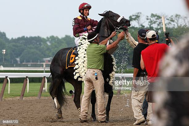 Jockey Alan Garcia watches as his horse Da' Tara is washed down after his victory at Belmont Park during the running of the 140th Belmont Stakes in...