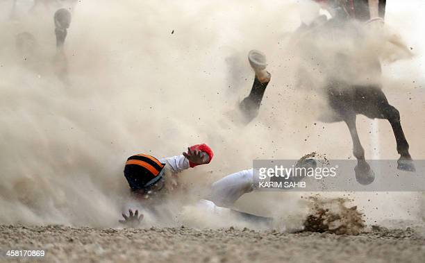 A jockey and his horse fall as they compete in a purebred Arabian horse race on the sidelines of the Mazayin Dhafra Camel Festival in the desert 150...