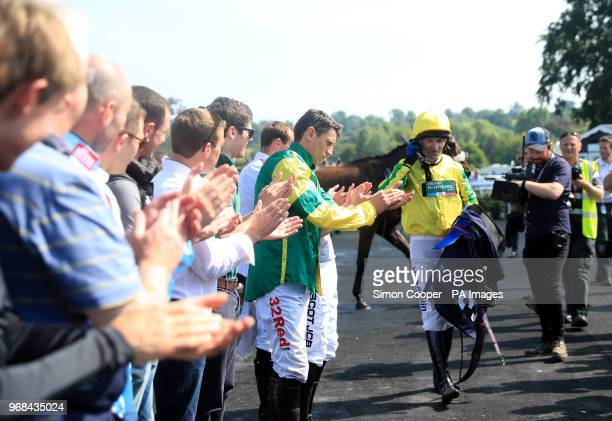 Jockey Andrew Thornton is applauded by the other jockeys in the parade ring after his final race as a jockey at Uttoxeter Racecourse