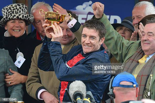 Jockey Barry Geraghty celebrates with the trophy after winning the Cheltenham Gold Cup Steeple Chase on horse 'Bobs Worth' during the last day of the...