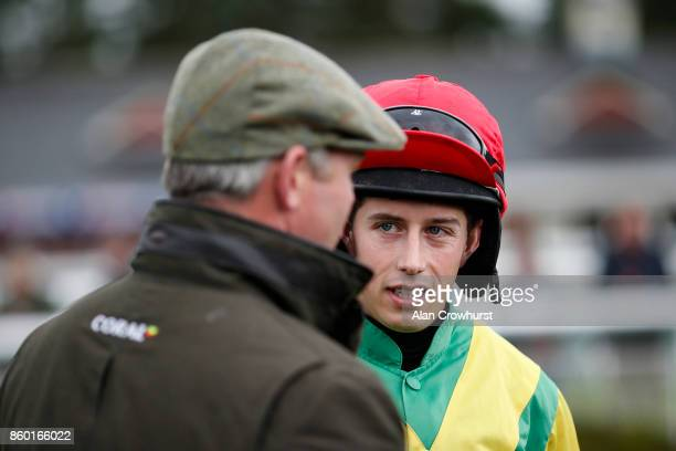 Jockey Bryan Cooper in the Ann Alan Potts colours chats to Joe Tizzrad at Ludlow racecourse on October 11 2017 in Ludlow England