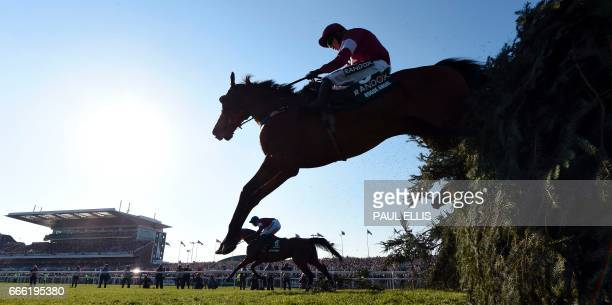 Jockey Bryan Cooper riding Rogue Angel jumps 'The Chair' during the Grand National horse race on the final day of the Grand National Festival horse...