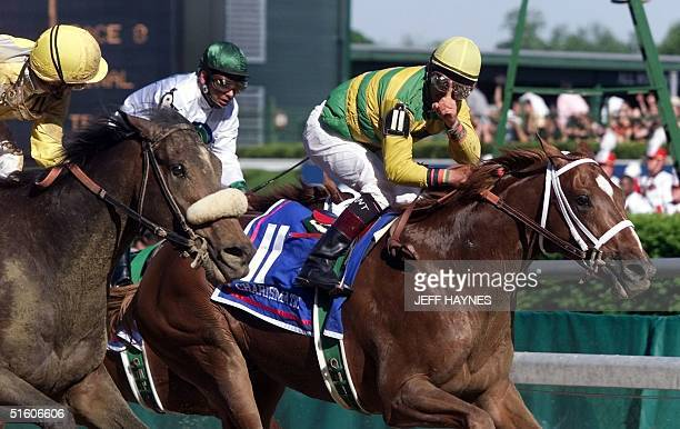 Jockey Chris Antley aboard Kentucky Derby winner Charismatic holds his finger showing number one to second place finisher Menifee and jockey Pat Day...
