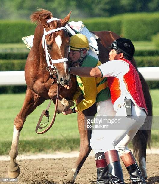 Jockey Chris Antley an a track worker helps Charismatic after crossing the finish line 05 June 1999 during the 131st running of the Belmont Stakes in...