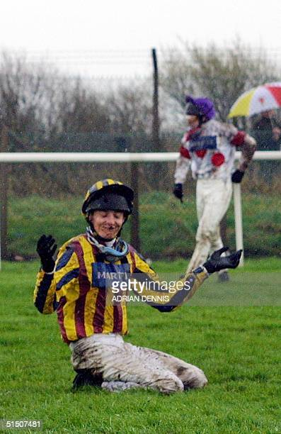 Jockey Chris Maude holds his arms in despair after falling at Becher's Brook fence on the first lap of the Grand National steeple Chase race at...