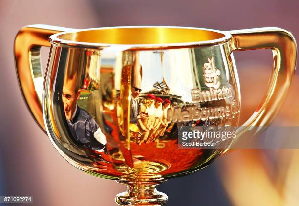 Jockey Corey Brown and trainer Joseph O'Brien are reflected in the Melbourne Cup trophy after Rekindling ridden by jockey Corey Brown won race 7 the...