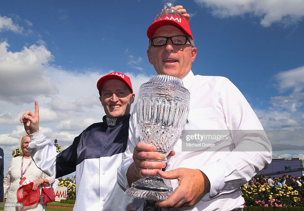 Jockey Craig Newitt (L) and trainer Mick Price celebrate their win with Tarzino in race 7 The AAMI Victoria Derby with a fan on Derby Day at Flemington Racecourse on October 31, 2015 in Melbourne, Australia.