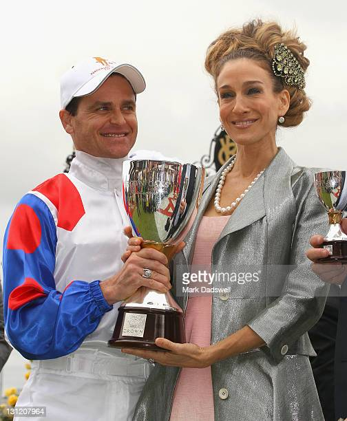 Jockey Danny Nikolic poses with the Crown Oaks trophy after receiving it from Sarah Jessica Parker during Crown Oaks Day at Flemington Racecourse on...