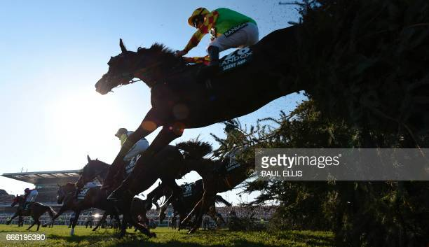 Jockey Davy Russell riding Saint Are jumps 'The Chair' during the Grand National horse race on the final day of the Grand National Festival horse...