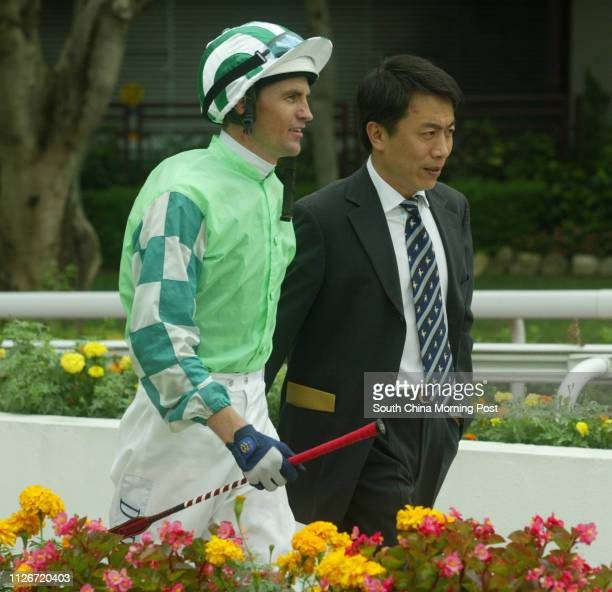 Jockey Dwayne Dunn accompanied by trainer Ricky Yiu returns to scale after mounting Congee King to win the Race 4 at Sha Tin Racecourse 18 May 2003