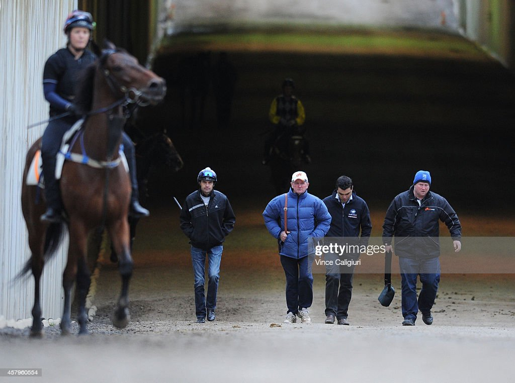 Jockey Dwayne Dunn and Trainer John Hawkes ( 2nd L) walk back to stables after a trackwork session at Flemington Racecourse on October 28, 2014 in Melbourne, Australia.