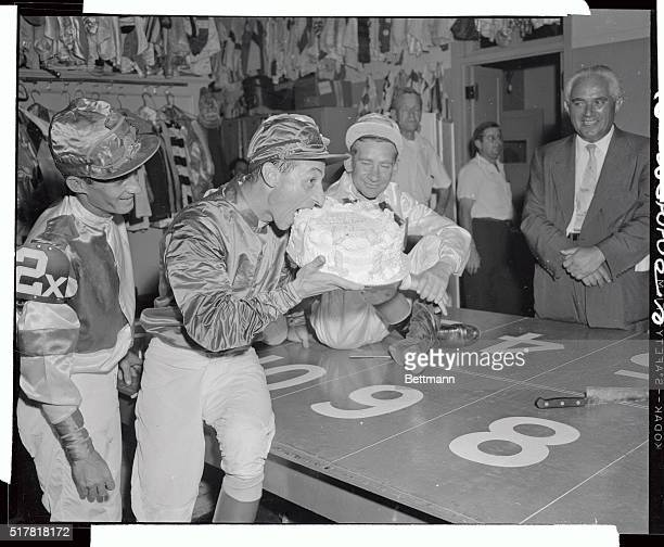 Jockey Eddie Arcaro celebrates his 40th birthday a day early by biting into a huge cake shortly after he rode Nashua into first place in the Widener...