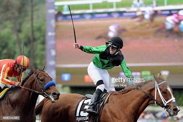 Jockey Florent Geroux atop Work All Work celebrates as he crosses the finish line ahead of jockey Martin Garcia atop Secret Circle in the 2014...