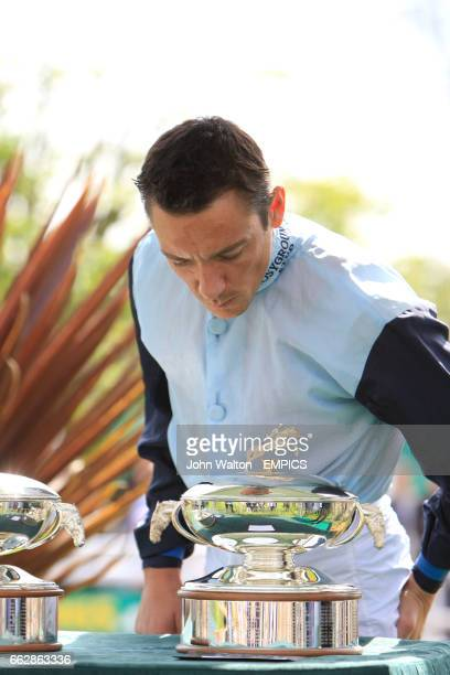 Jockey Frankie Dettori presents Chanel wife of jockey Tony McCoy with The Champion Jockey Trophy during the Gold Cup Meeting at Sandown Park