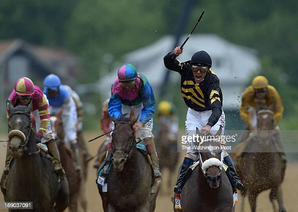 Jockey Gary Stevens raises up and cheers after finishing first on Oxbow during the 138th Running of the Preakness Stakes at Pimlico Race Course in...