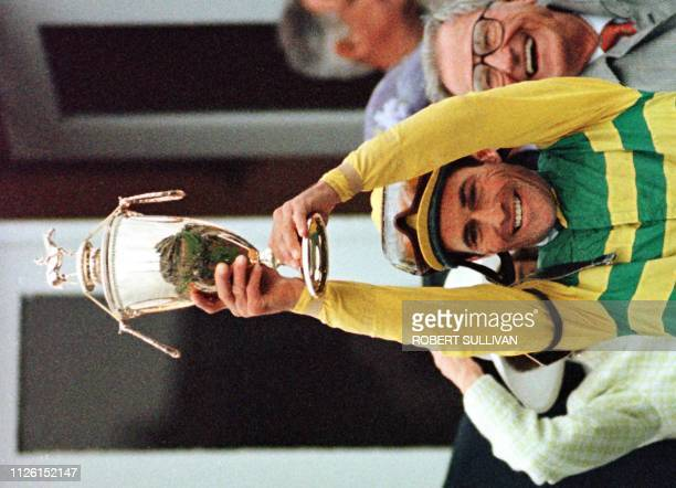 Jockey Gary Stevens winner of the Kentucky Derby aboard Silver Charm raises the trophy after winning the 123rd running of the race 03 May at...