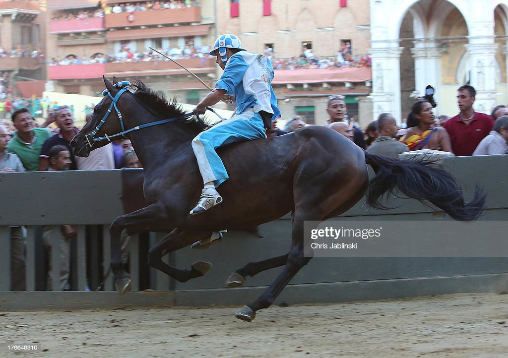Jockey Giovanni Atzeni (L), known as Tittia, rides his horse bareback on his way to winning the Palio dell'Assunta horse-race at Piazza del Campo square on August 16, 2013 in Siena, Italy. The Palio races in Siena, in which riders representing city districts compete, and takes place twice a year in the summer in a tradition that dates back to 1656.