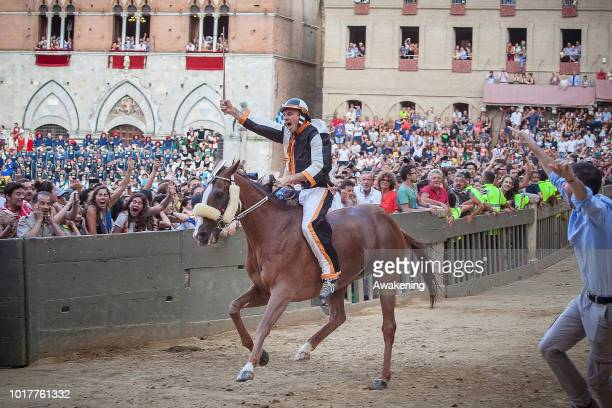 'Contradaioli' of contrada Lupa celebrates the victory with the 'cencio' at the historical horse race Palio di Siena on August 16 2018 in Siena Italy...
