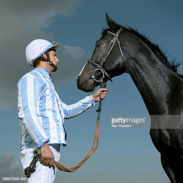 jockey holding horse's reins, profile - riding hat stock pictures, royalty-free photos & images