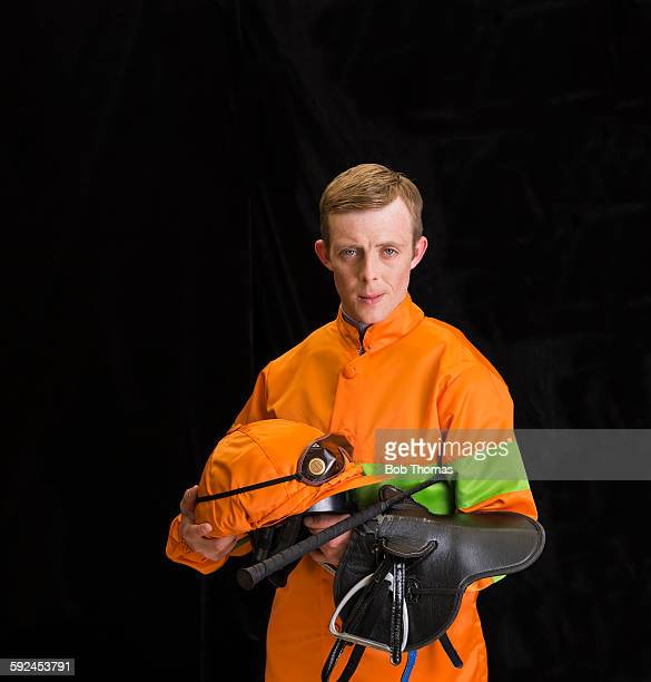 jockey holding saddle and helmet - jockey silks stock pictures, royalty-free photos & images