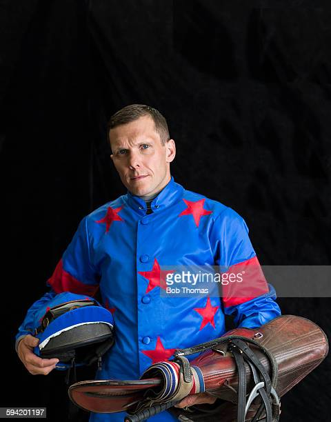 Jockey Holding Saddle and Helmet