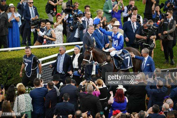 Jockey Hugh Bowman celebrates on the back of champion race horse Winx after her final race to victory in the Longines Queen Elizabeth Stakes during...