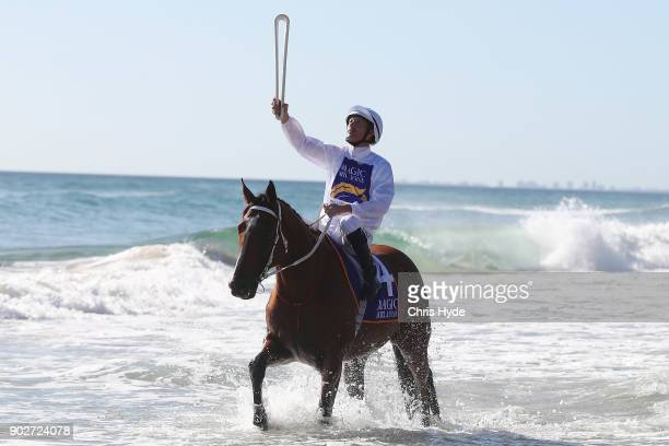 Jockey Hugh Bowman holds The Commonwealth Games Queen's Baton while riding on Surfers Paradise beach during the Magic Millions Barrier Draw on...