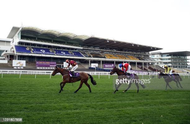 Jockey Jack Kennedy on Minella Indo rides past empty stands ahead of second-placed jockey Rachael Blackmore on A Plus Tard and third-placed jockey...