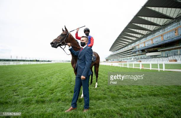 Jockey James Doyle celebrates after his victory on The Queens horse Tactical in The Windsor Castle Stakes and is held by his groom Nathan Cheshire...