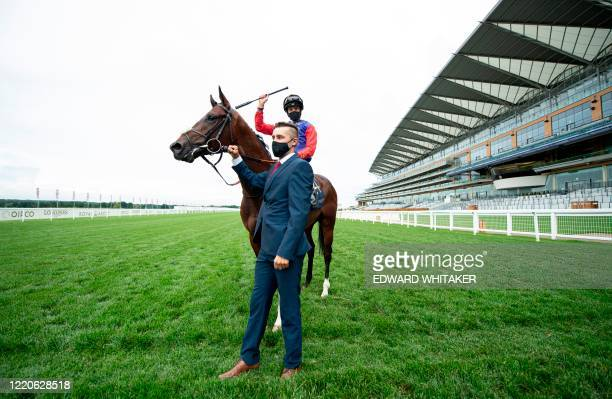 Jockey James Doyle wearing the Queen's silks riding Tactical celebrates after winning The Windsor Castle Stakes on day two of the Royal Ascot horse...