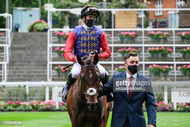 Jockey James Doyle wearing the Queen's silks riding Tactical is led after winning The Windsor Castle Stakes on day two of the Royal Ascot horse...
