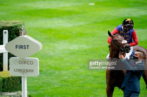Jockey James Doyle wearing the Queen's silks riding Tactical is led to the winner's enclosure after winning The Windsor Castle Stakes on day two of...