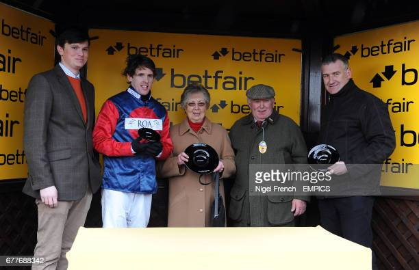 Jockey Jason Maguire and Trainer Donald McCain collect their trophies after winning the Betfair. Don't Settle For Less Novices' Chase with Our Mick
