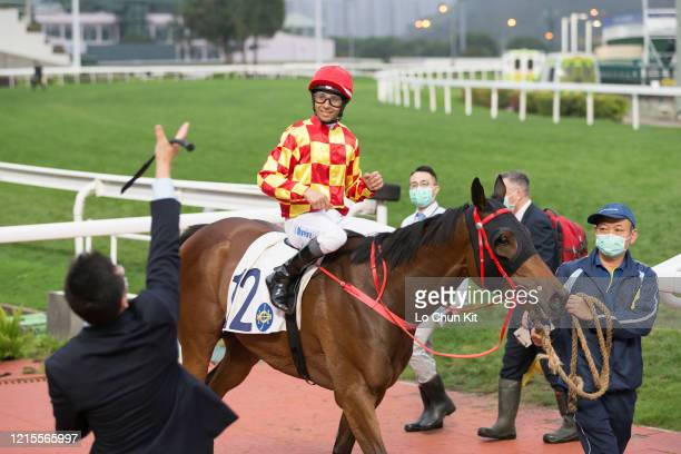 March 29 : Jockey Joao Moreira throws his whip in delight after winning on Shining Ace during the Race 10 Chak On Handicap at Sha Tin Racecourse on...