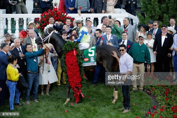 Jockey John Velazquez atop Always Dreaming pose for a photo in the winner's circle after winning the 143rd running of the Kentucky Derby at Churchill...