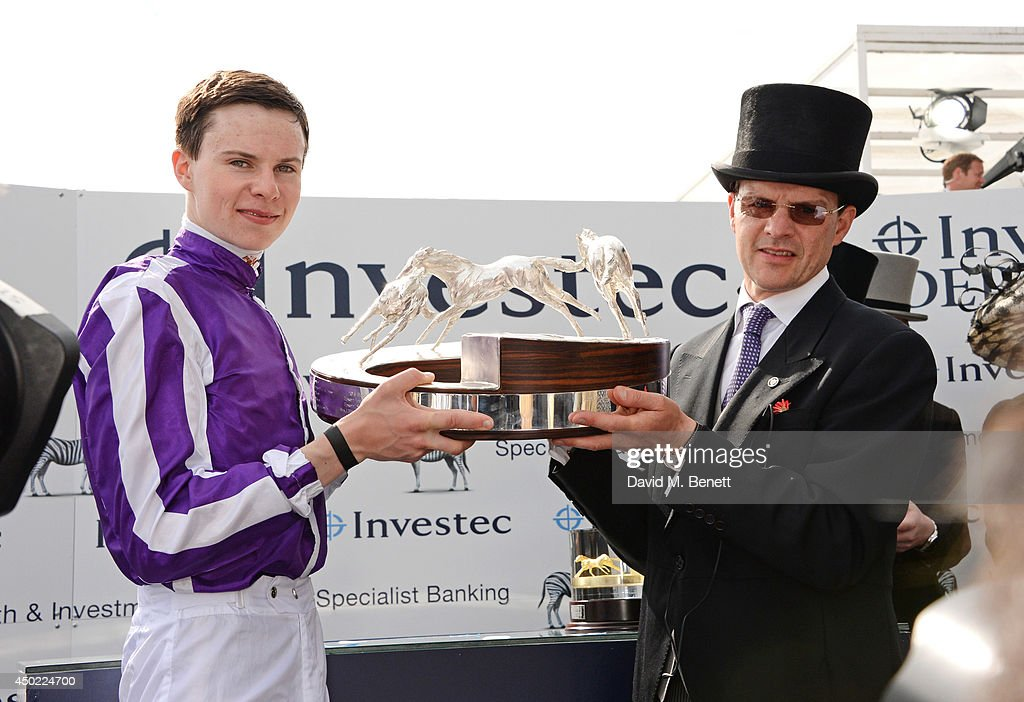 Jockey Joseph O'Brien (L) and trainer Aidan O'Brien celebrate their horse Australia's win of the Investec Derby during Derby Day at the Investec Derby Festival at Epsom Downs Racecourse on June 6, 2014 in Epsom, England.